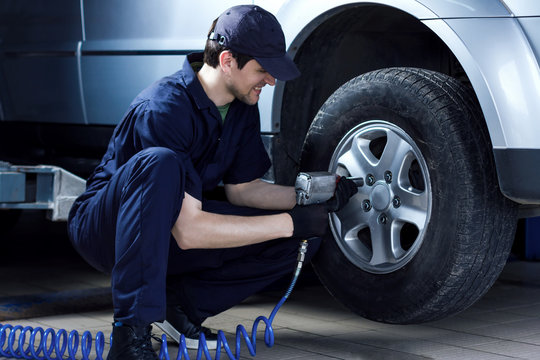 Smiling mechanic in blue jumpsuit is repairing car at service station garage. Repairman is removing wheel by electric wrench, tyre mounting equipment at workshop auto repair shop. Tire fitting concept