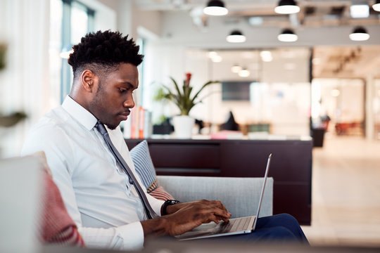 Businessman Working On Laptop At Desk In Shared Workspace Office