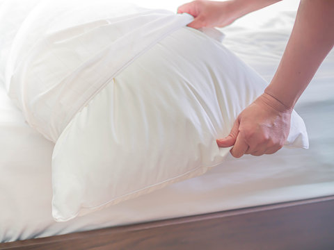 White pillow on the bed in the bedroom with woman 's hand who are making the room.