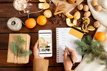 Female hands holding smartphone and making list of Christmas gifts