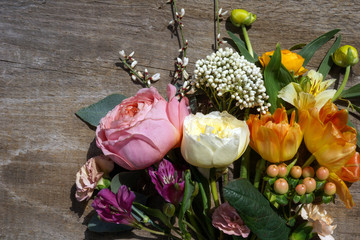 Horizontal image of fresh cut flowers and greenery on a weathered wood background with copy space