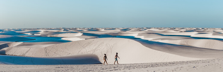 travel couple trek across giant sand dunes with lagoons in Lencois Maranhenses, one of the most stunning tourist attracts in North-East Brazil