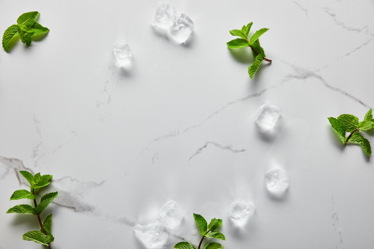top view of green fresh mint and ice cubes on marble surface
