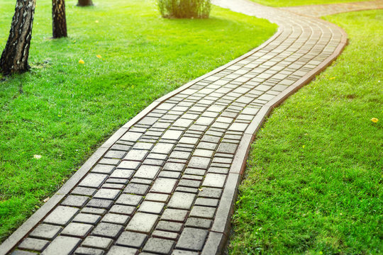 Slab stone paved path way along green grass lawn at park or backyard. Walkway footpath road at house yard garden