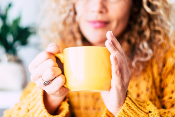 Close up on cup with tea or coffe drink inside and beautiful defocused woman in background - concept of relax and healthy lifestyle with nice people - yellow colors mood Fototapete