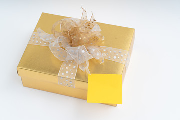 Blank adhesive note on gold gift box on white background