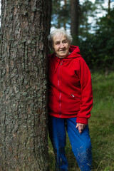 An old woman in a red jacket walks in a pine Park.