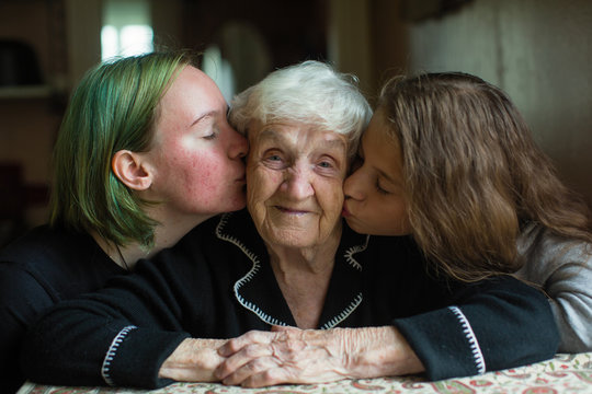 Two girls kissing grandmother