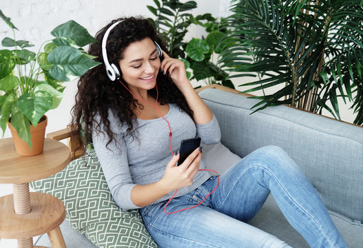 lifestyle and people concept: young woman at home and listening to music with headphones