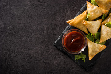 Samsa or samosas with meat and vegetables on black background. Traditional Indian food. Top view. Copyspace