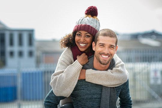 Couple enjoying piggyback ride in winter