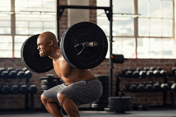 Mature strong man lifting weights at crossfit