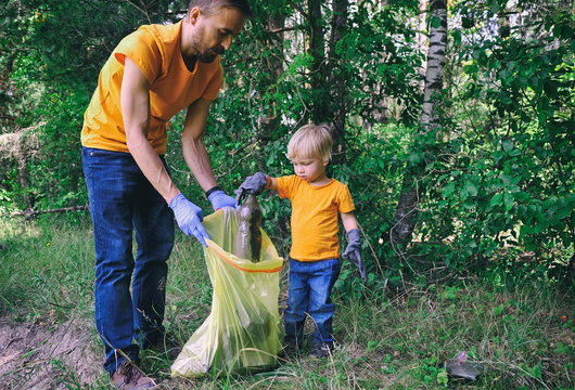 Volunteers activists picking up litter in the park. Father and his toddler son cleaning up forest to save environment from pollution