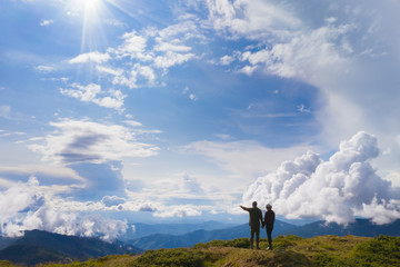 The couple standing on a mountain against beautiful clouds