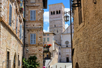 Fototapete - Medieval street in the old town of Assisi with the tower of the Cathedral of San Rufino in the background, Italy