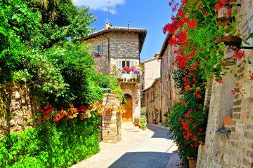 Flower filled medieval street in the beautiful old town of Assisi, Italy