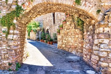 Wall Mural - Medieval buildings of the old town of Assisi through a picturesque stone arch, Italy