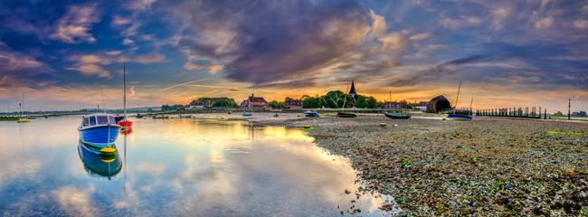 Bosham, UK - June 2, 2019:  Summer sunrise over the village of Bosham at low tide with the harbour and wadeway, West Sussex, UK Fototapete