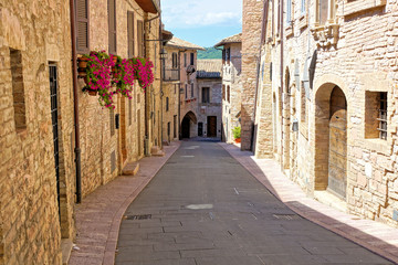 Fototapete - Stone buildings lining a beautiful medieval street in the old town of Assisi, Italy
