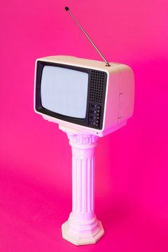 Old analog TV displaying noise against bright pink background. Vaporwave.