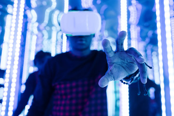 Black man in VR touching air in neon lights