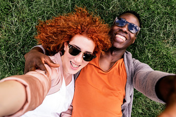Smiling young couple lying on grass and taking selfie