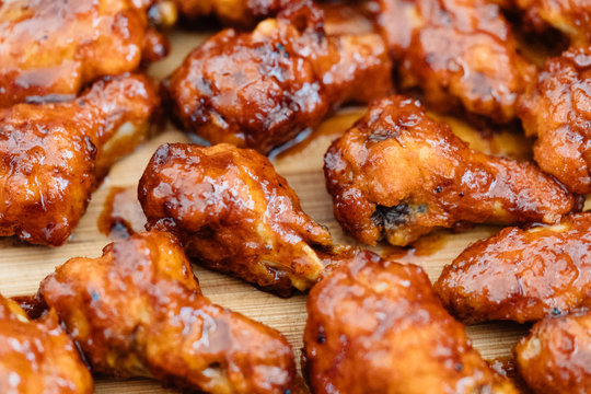 Crispy barbecue chicken wings covered in a sweet and tangy bbq sauce and served at a cookout.