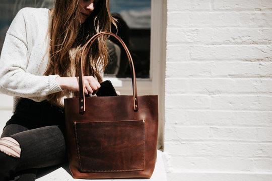 Woman putting phone in bag