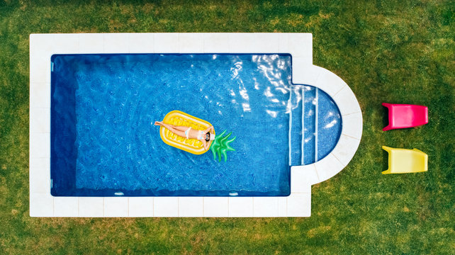 Little girl lying on a pineapple-shaped float in a swimming pool