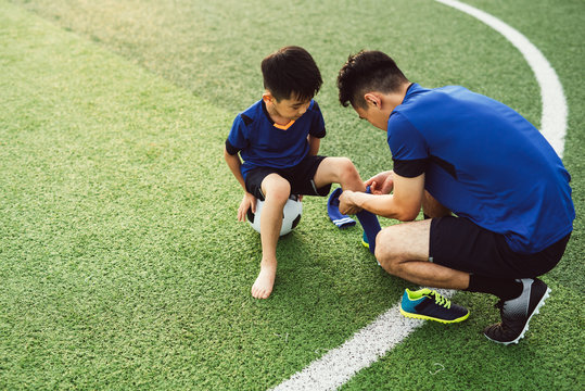 Father putting socks on his son on soccer field