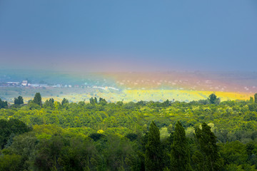 Wall Mural - Natural rainbow over green trees, summer city landscape