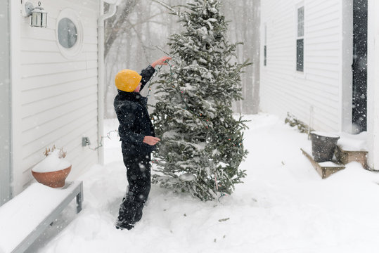 boy with yellow hat putting lights on a Christmas tree in the snow