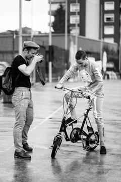 Man taking photograph of woman riding bicycle
