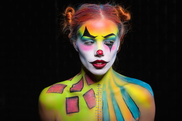 Beautiful lady with a face painting clown posing in the studio.