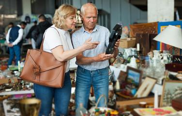 Elderly couple in flea market chooses antique items Fototapete