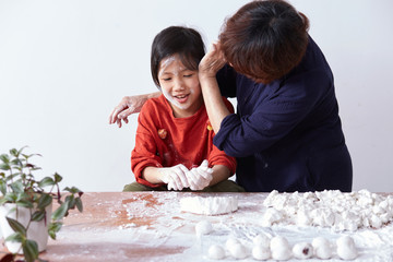 Asian grandmother and cute little granddaughter, happy to make Chinese dessert rice dumpling at home