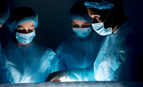 Surgeons performing surgical operation in dark operating room