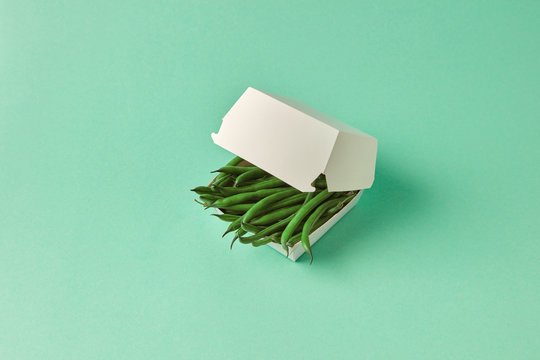 Paper lunch box with organic raw French beans on a green pastel