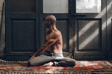 Shirtless man practicing yoga on carpet