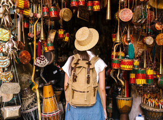 Woman exploring stall with oriental musical instruments