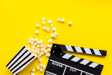 Go to the cinema with popcorn and clapperboard on yellow background top view