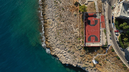 Aerial drone top view photo of Basket ball court near rocky seascape