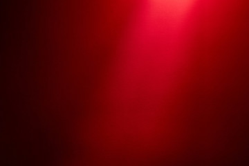 Light red ray of light on a dark red finely textured background