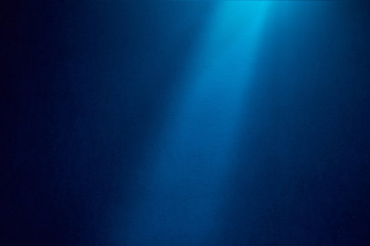 Light blue ray of light shines vertically on blue textured grungy background