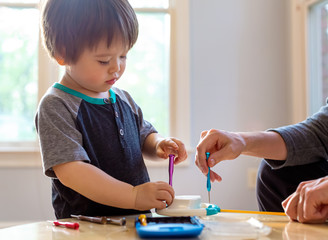 Toddler boy playing with tools and helping fix his toy