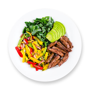 Tasty healthy beef lunch or dinner on white plate: grilled skirt steak, sauteed vegetables and avocado. Top view. Isolated.