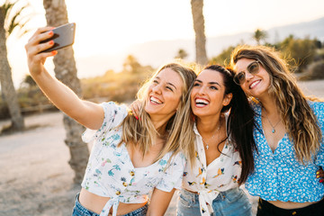 Group of three women friends making a selfie in a beach during a summer day. Friendship and holiday.
