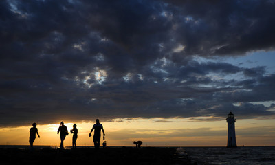People walk along the beach at sunset in New Brighton