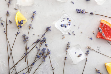 Lavender flowers with ice cubes and citrus slices on grey background