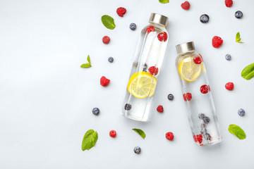 Fotobehang - Bottles of tasty infused water on light background